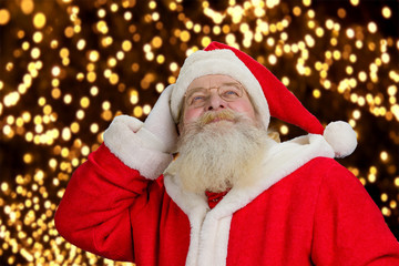 Portrait of happy Santa Claus. Senior Santa Claus looking upwards on festive lights background close up. Cheerful Santa Claus enjoying festive New Year atmosphere.