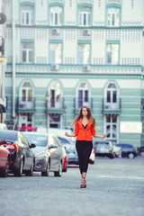 Fashionable look, hot day model of a young woman walking in the city, wearing a red jacket and black pants, blond hair outdoors over the city warm background