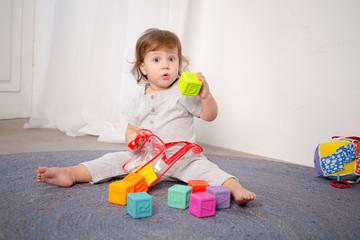 Little happy girl playing with toy on floor. Kindergarten.