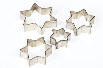 Four star shaped Christmas cookie cutters over white. Tin biscuit cutters, tool to cut cookie dough in particular shapes and to make cutouts. Hexagram shaped and six pointed geometric star figures.