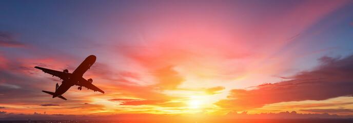 Fototapeta The silhouette of a passenger plane flying in sunset.