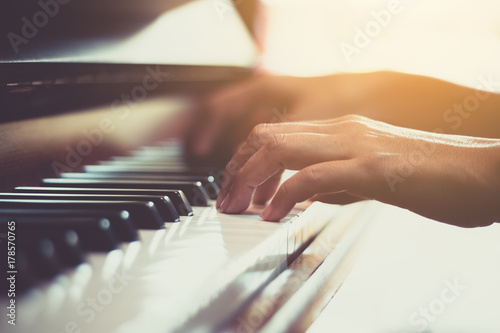 Close up of happy woman's hand playing the piano in the