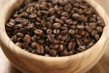 roasted coffee beans in wood bowl on table