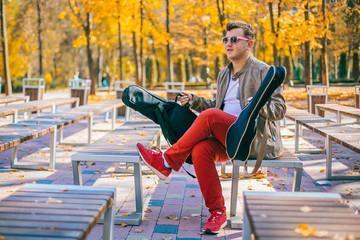 Young man are playing bass ukulele on the park autumn park near lake. Basking guy at the street. Two case for guitars ukulele.