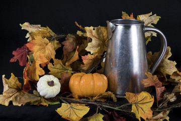 Handmade metal pitcher in fall setting