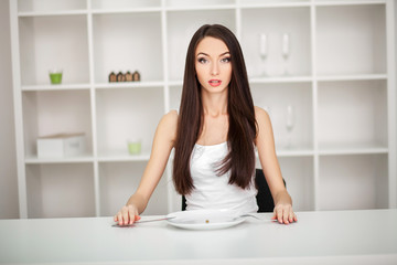 Suffering from anorexia. Image of girl trying to put a pea on the fork