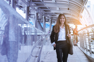 attractive business woman happy and smile while walking in modern downtown to work at morning with sunrise.