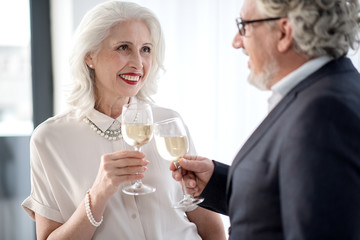 Glad senior woman and man clinking glasses of alcohol beverage