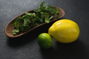 Mint leaf and sweet limes on black background