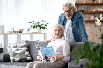 Cheerful senior married couple reading magazine in living room