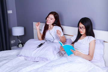 two woman reading a book and using smart phone on bed in bedroom