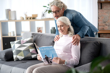 Happy senior man and woman entertaining with journal at home