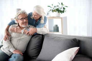 Happy senior loving couple resting in living room