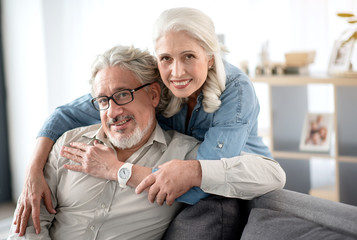 Joyful mature man and woman relaxing at home together