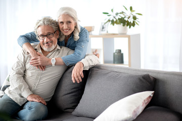 Cheerful mature husband and wife resting in living room
