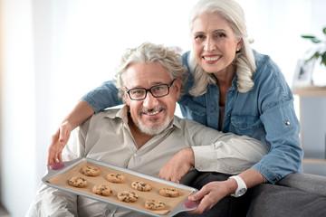 Joyful senior woman giving sweets to woman at home