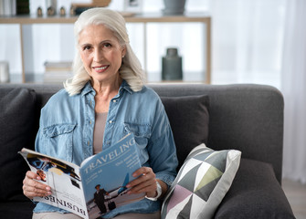 Happy mature woman reading magazine in living room