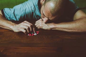 Depressed man suffering from suicidal depression want to commit suicide by taking strong medicament drugs and pills and he is cover his face with his hand