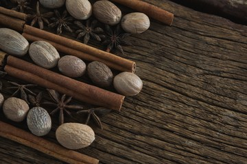 Nutmeg, star anise and cinnamon sticks arranged on wooden table