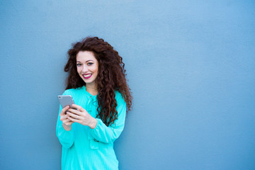 Happy young woman on the mobile phone by a colorful wall