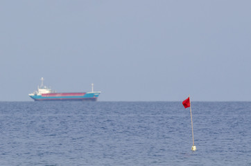SEASCAPE -  Red fishing flag and freighter on the horizon
