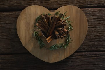 Cinnamon sticks and rosemary on a heart shaped chopping board
