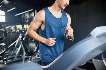 Mid section portrait of muscular young man running on treadmill in modern gym during cardio workout