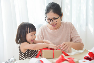 Young mother and her daughter wrapping a gift box.