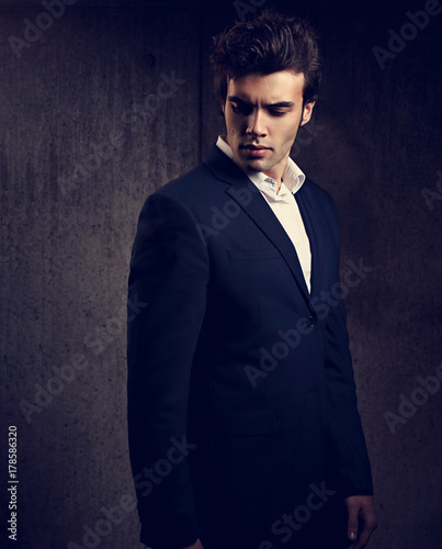 46c40610 Sexy handsome male model posing in blue fashion suit and white style shirt  looking down on dark shadow background. Toned color fashion portrait