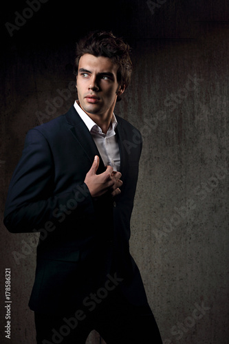 6da0b3a0 Sexy handsome male model posing in blue fashion suit and white style shirt  on dark shadow background