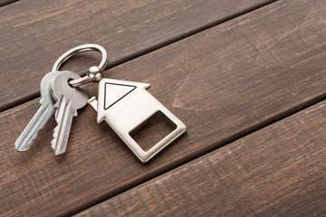 Bunch of keys with house shaped keychain on brown wood