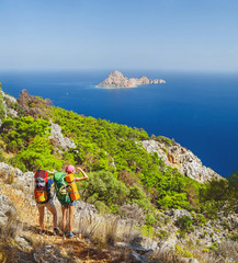 Two hiker woman walk along Lycian Way trail in Turkey and admiring great view on island in a Meditteranean sea