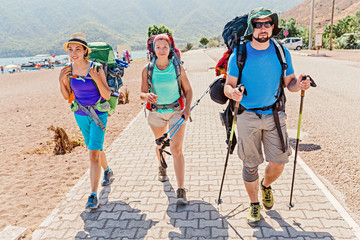 group of young happy friends students traveling along the Lycian trail with backpacks at the coastal road in the forest. Hiking and trekking in Turkey concept