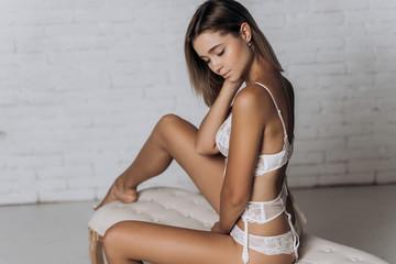 Sexy woman in underwear posing. Beautiful girl in white wedding lingerie.