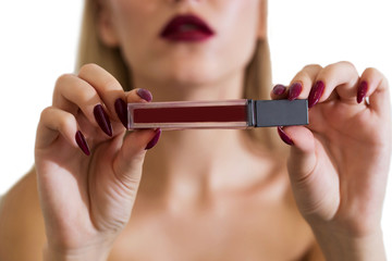 Beautiful blonde with dark lips, lipstick in hand, Holds and shows. Advertising of cosmetics, makeup, close-up