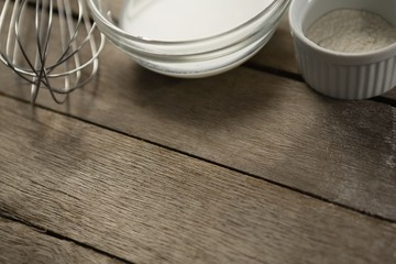 Cropped image of milk and flour in bowls by wire whisk