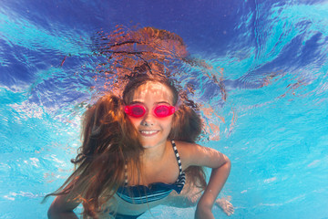 Happy girl in pink goggles swimming under water