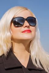 Closeup shot of blonde model  wears sunglasses, posing in black coat in sun light
