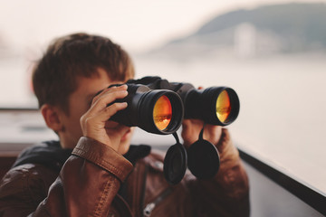 Little boy watching, looking, gazing, searching for by binoculars during trip