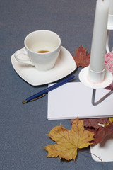 Forged metal candlestick with candles. There is an open notepad and a pen. A cup with unapproved coffee. Fallen autumn leaves of yellow and red are scattered on the surface.