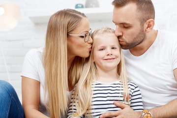 Happy family at home in love kissing child