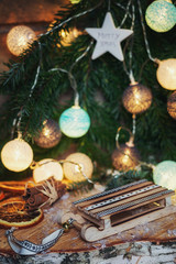Small colorful wooden sledge in front of a Christmas branch decorated with illuminated christmas balls