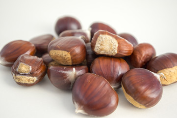 Raw sweet chestnuts scattered on a white background, tasty and healthy brownish nuts