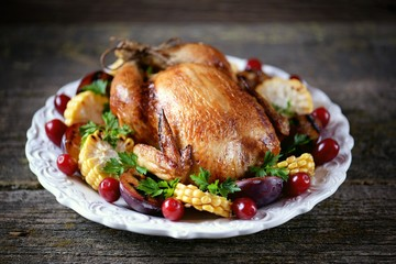 Grilled chicken on Thanksgiving day with corn, plum, dogwood and parsley.