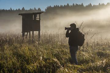 Mann fotografiert einen Jägerstand im Nebel