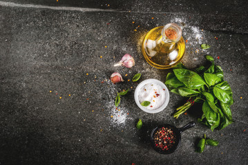 Ingredients for cooking dinner, spices, dark stone table. Basil leaves, olive oil, garlic, salt and pepper, Copy space top view