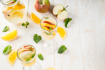 Drinks and cocktails. White autumn sangria with apples, orange, mint and white wine. In glasses for champagne, in a pitcher, on a white wooden table. Copy space top view