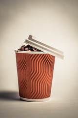 A paper glass filled with coffee beans and a white lid on it