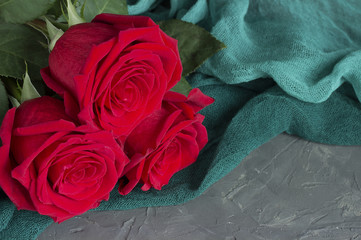 Three red roses on gray concrete background.