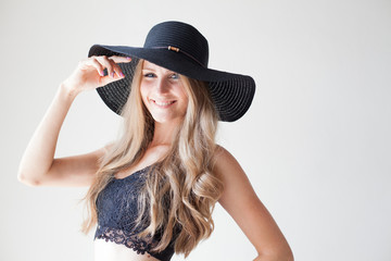 fashionable girl blonde with blue eyes in a hat with a brim